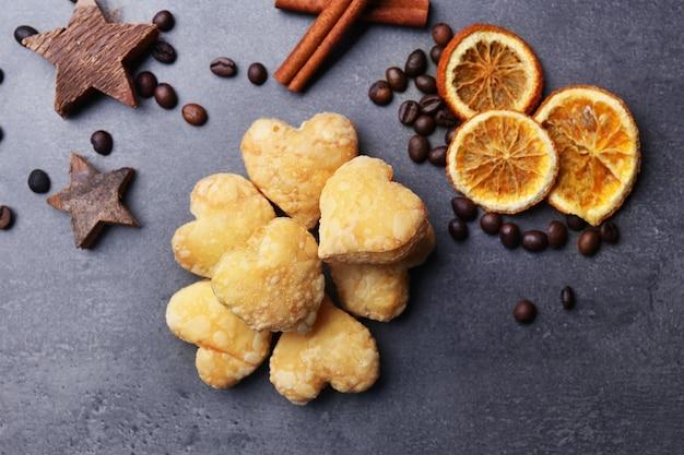 Hartvormige koekjes met gedroogde kruiden op donkergrijs