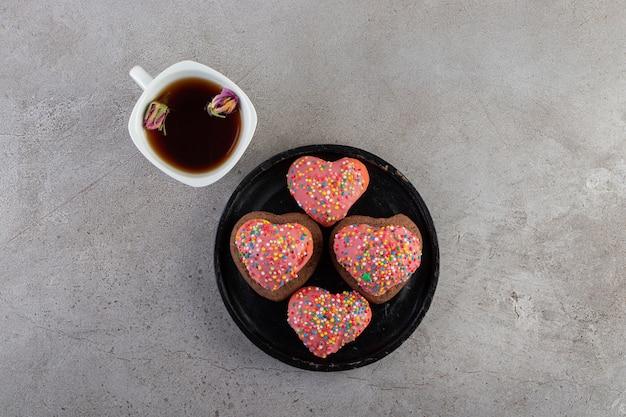Hartvormige koekjes met hagelslag en een kopje thee op een stenen tafel.