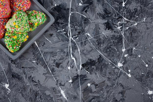 Hartvormige koekjes met kleurrijke hagelslag op een houten bord.