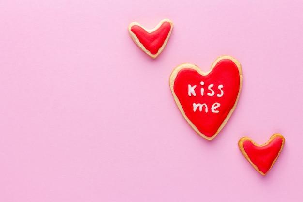 Hartvormige koekjes met rode suikerglazuur en woordliefde voor st valentine-dag op roze achtergrond