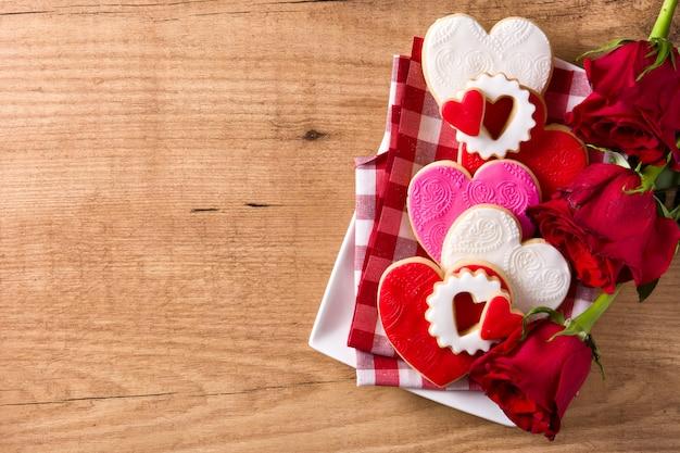 Hartvormige koekjes voor valentijnsdag met rozen op houten, kopie ruimte