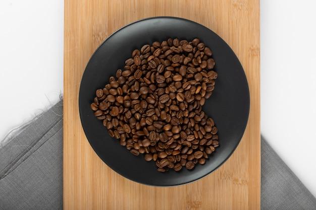 Hartvormige koffiebonen in een schoteltje