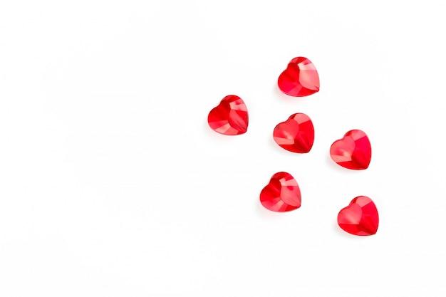 Hartvormige kristallen op een wit gestructureerd oppervlak, stemming van tederheid en liefde, valentijnsdagsymbolen