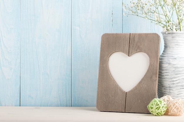 Hartvormige lege fotolijst en lentebloemen op blauwe houten achtergrond