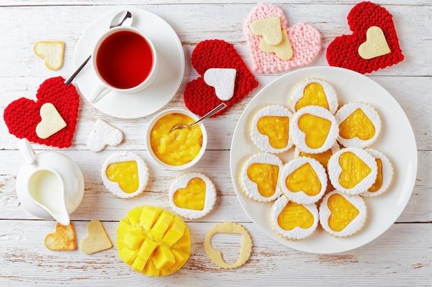 Hartvormige linzer koekjes gevuld met mango jam op een witte plaat op een houten tafel versierd met rode en roze gebreide hart servetten. een kopje thee, mango en een kan met room op tafel, flatlay