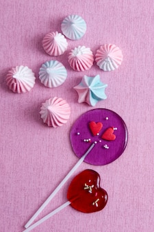Hartvormige lollies en marshmallows op roze achtergrond