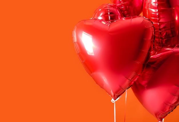 Hartvormige luchtballonnen op oranje achtergrond