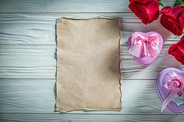 Hartvormige metalen geschenkdozen rode rozen vintage papier op hout