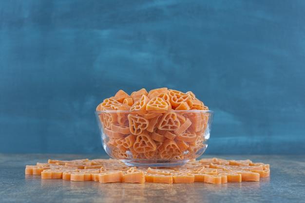 Hartvormige pasta's in en rond de kom, op het marmeren oppervlak.