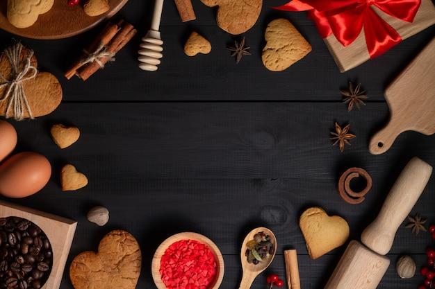 Hartvormige peperkoekkoekjes, kruiden, koffiebonen en bakbenodigdheden.