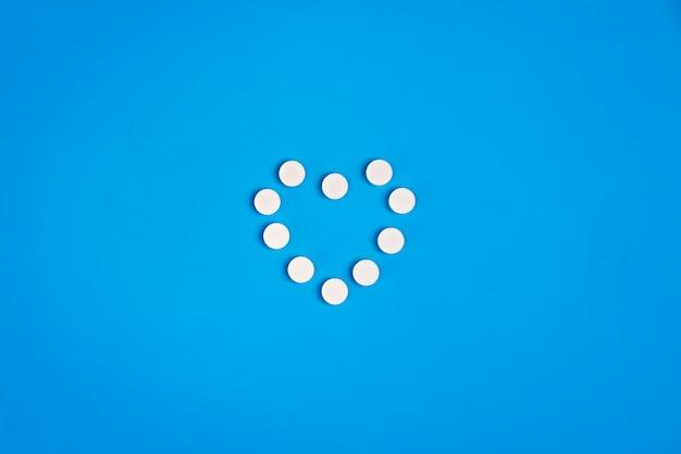 Hartvormige pillen op een blauwe achtergrond, bovenaanzicht.