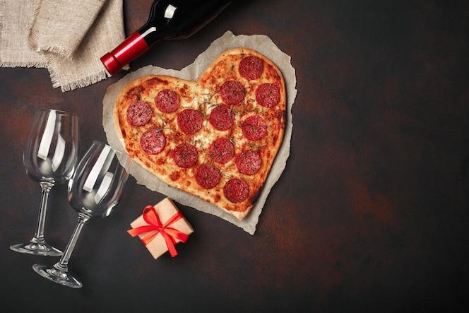 Hartvormige pizza met mozzarella, sausagered, wijnfles, twee wijnglas, geschenkdoos op roestige achtergrond