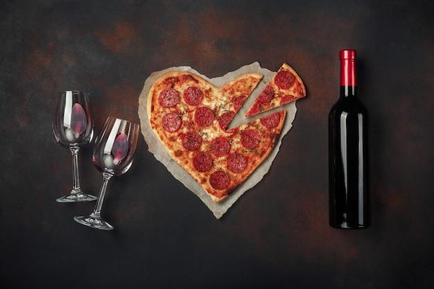 Hartvormige pizza met mozzarella, worst, wijnfles en twee wijnglas. de groetkaart van de valentijnskaartendag op roestige achtergrond.