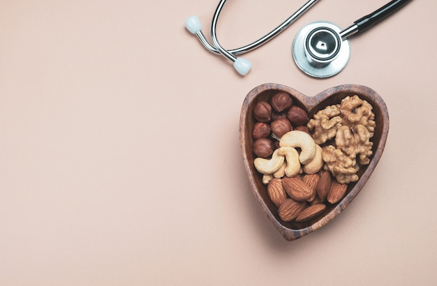Hartvormige plaat met handvol gemengde noten en medische stethoscoop op beige achtergrond