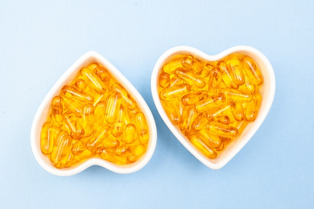 Hartvormige plaat met visolie capsules omega 3, gezond product en supplement concept close up, plat lag