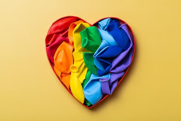 Hartvormige regenboog lgbtq vlag tegen gele achtergrond trots maand