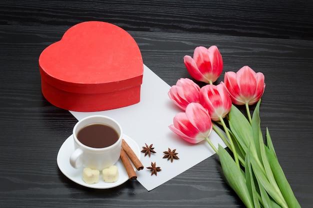Hartvormige rode doos, roze tulpen, grijs blad en een koffiemok