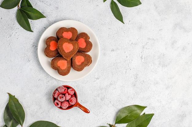 Hartvormige valentijn cookies met bevroren frambozen op lichte achtergrond