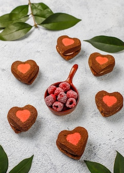 Hartvormige valentijn koekjes met bevroren frambozen op licht
