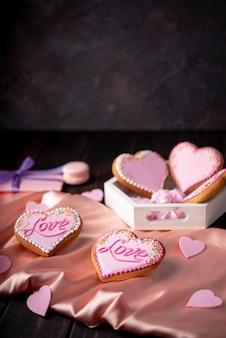Hartvormige valentijnsdag koekjes op satijn met kopie ruimte