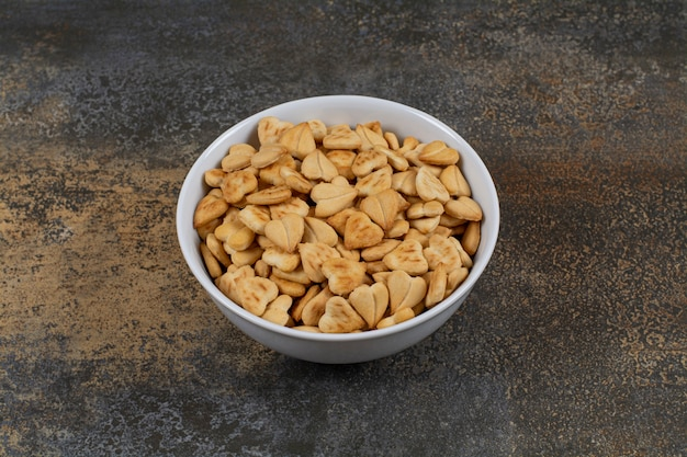 Hartvormige zoute crackers in witte kom.