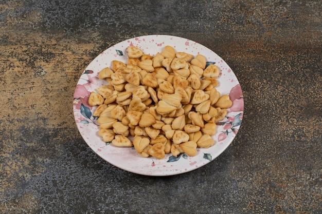 Hartvormige zoute crackers op kleurrijke plaat.