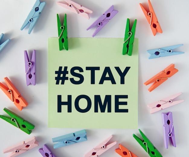 Hashtag blijf thuis - tekst op een notitieblad en kleurrijke wasknijpers