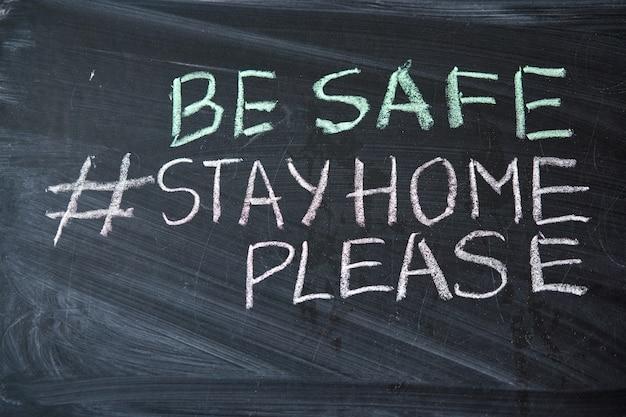 Hashtag blijf thuis. waarschuwing bij uitbraak. geschreven wit krijt op bord in verband met epidemie van coronavirus wereldwijd. covid 19 pandemische tekst op zwarte achtergrond met vrije ruimte.