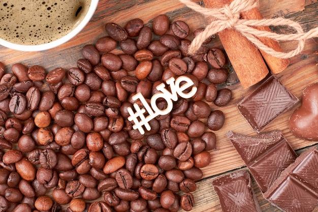 Hashtag liefde inscriptie in de buurt van snoepjes. kaneelstokjes en koffiebonen. aromatische start van de dag.