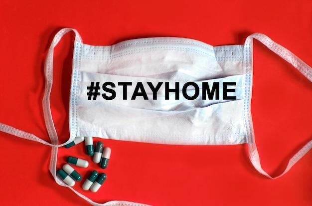 Hashtag stayhome - tekst op een beschermend gezichtsmasker, tabletten op een rode achtergrond