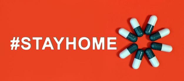 Hashtag stayhome - witte tekst op een rode achtergrond met pillencapsules