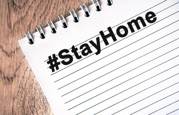 Hashtag stayhome - zwarte tekst op een wit notitieboekje met lijnen op een houten tafel