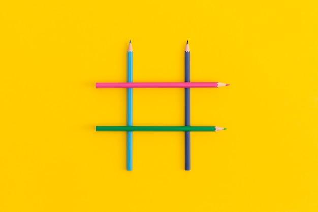 Hashtags teken gemaakt van kleurpotloden op gele achtergrond