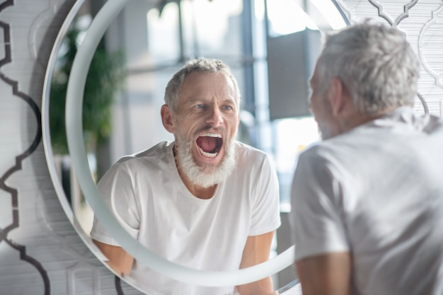 Havaing plezier. een man die grappige gezichten trekt in de buurt van de spiegel