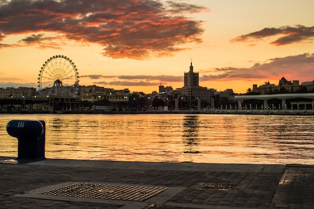 Haven bij zonsondergang met het reuzenrad achtergrond