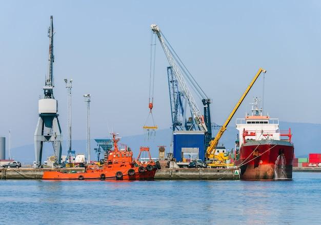 Havenkranen die industrieel vrachtschip in zeehaven laden