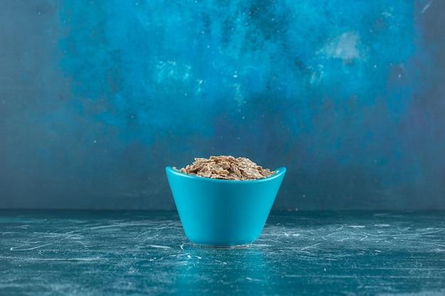 Haver muesli in een kom, op de blauwe tafel.