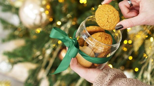 Haverkoekjes in een glazen pot. tegen de achtergrond van kerstdecor