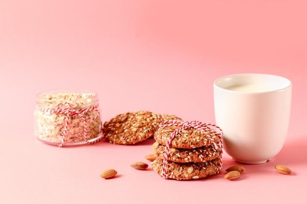 Havermeel chip cookies, moer, kopje melk op een roze achtergrond.