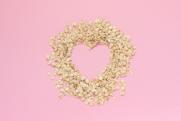 Havermeel in vorm van hart met lege ruimte voor tekst op roze achtergrond. dieet concept