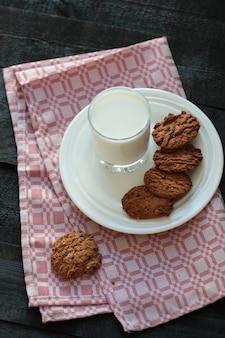 Havermeelkoekjes met een glas melk op de rode handdoek.