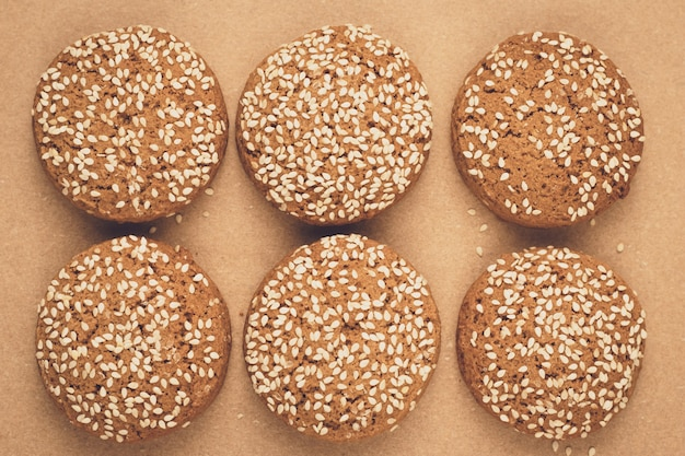 Havermeelkoekjes op bakpapier. handgemaakte bakkerij met sesamzaadjes. bruine achtergrond. een groep koekjes.