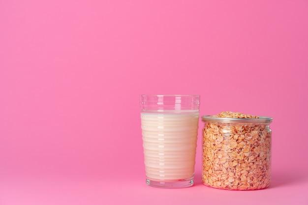 Havermelk in glaswerk en droge havervlokken op roze dichte omhooggaand als achtergrond