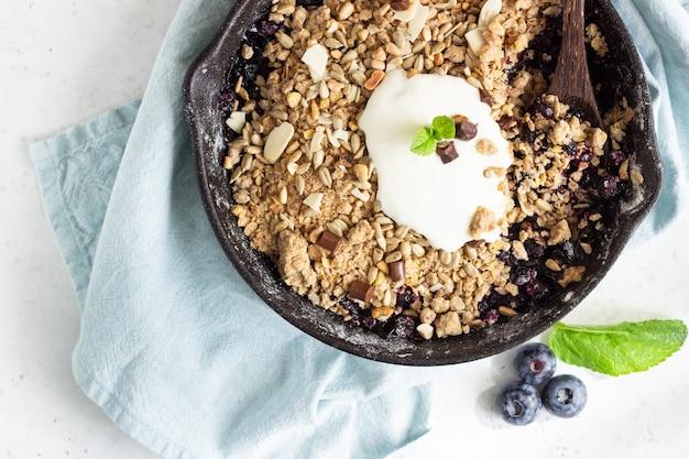 Havermout crumble in gietijzeren pan met verse bosbessen en natuurlijke yoghurt.