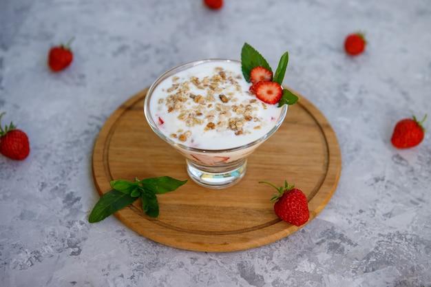Havermout dessert met aardbeien. gezond ontbijt van aardbeiparfait met vers fruit, yoghurt en granola op een grijze lijst. detailopname.