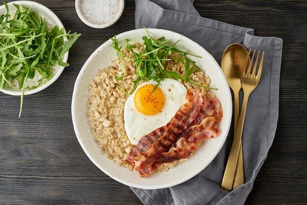 Havermout, gebakken ei en gebakken spek. balans van eiwitten, vetten, koolhydraten. detailopname