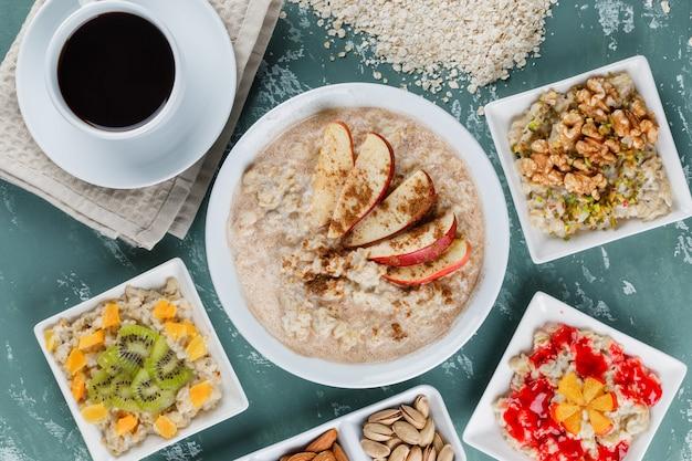 Havermout in borden met fruit, jam, noten, kaneel, koffie, havervlokken