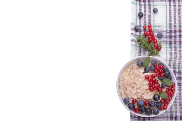 Havermout met bessen in een kom op een witte geïsoleerde achtergrond. ontbijt. gezond eten