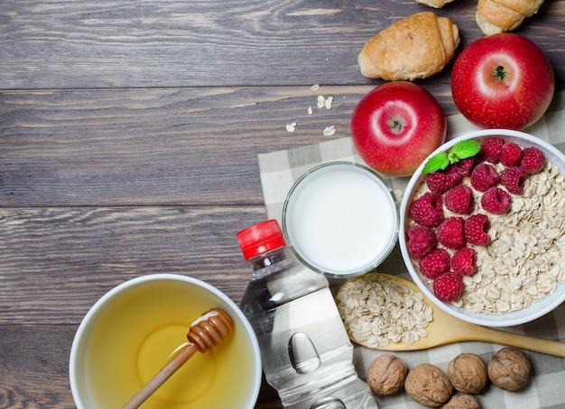 Havermout met frambozen, melk in een glas, honing, mineraalwater in een fles, walnoot, croissant, rode appels.