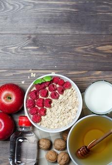 Havermout met frambozen, melk in een glas, honing, mineraalwater in een fles, walnoot, rode appels.
